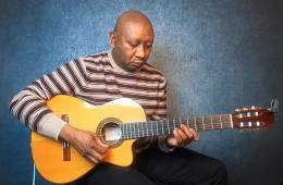 ron jackson seated with a guitar