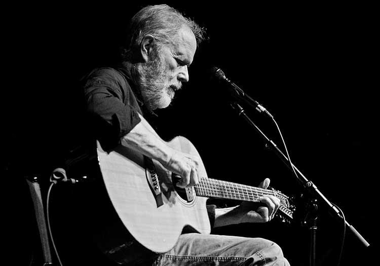 black and white photo of a seated Leo Kottke playing a 12-string acoustic guitar onstage