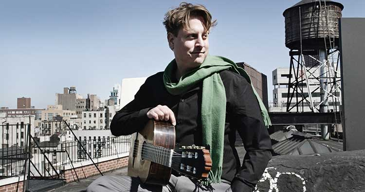 Classical guitarist Jason Vieaux poses outside on a rooftop on a clear day holding a nylon-string guitar