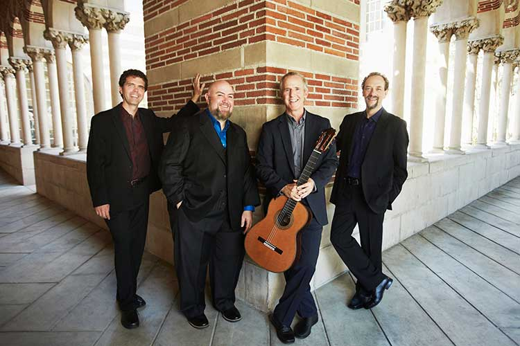 Los Angeles Guitar Quartet members Matthew Greif, Scott Tennant, John Dearman, and William Kanengiser pose for a photo in front of a brick support beam and ornately carved columns