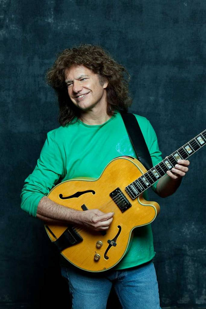 Guitarist Pat Metheny, wearing a green long-sleeve shirt, smiles as he plays a chord on an Ibanez archtop guitar