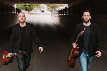guitarists Adam Cicchillitti and Steve Cowan walking on a road