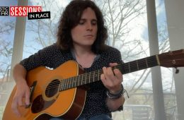 """Hamish Anderson performing """"Morning Light"""" on his acoustic guitar in front of a window"""