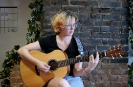 kate koenig plays a I-vi-IV-V7-I progression on an acoustic guitar
