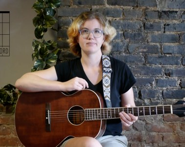chord by chord instructor kate koenig seated with acoustic guitar in front of a brick background