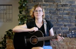 Chord by Chord instructor Kate Koenig, seated with guitar in front of brick backdrop