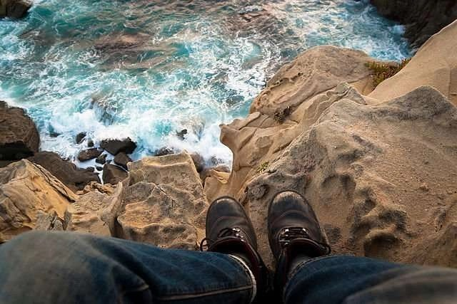 standing on edge of a cliff over water