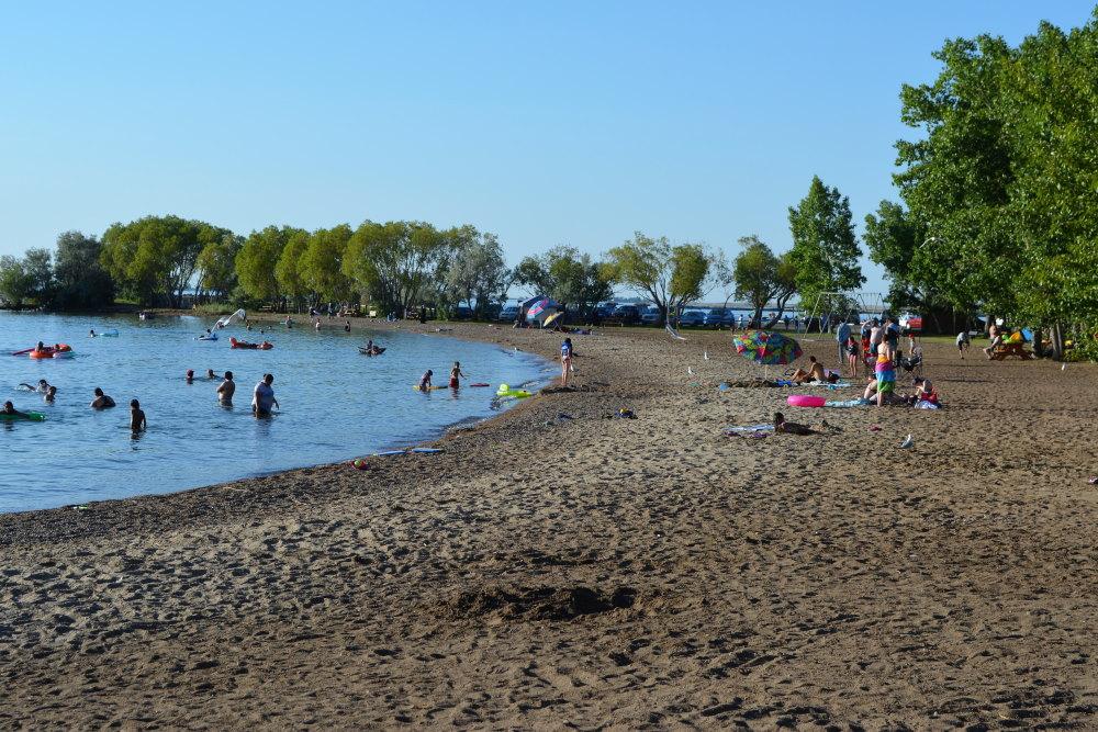 scattered people enjoying sandy beach