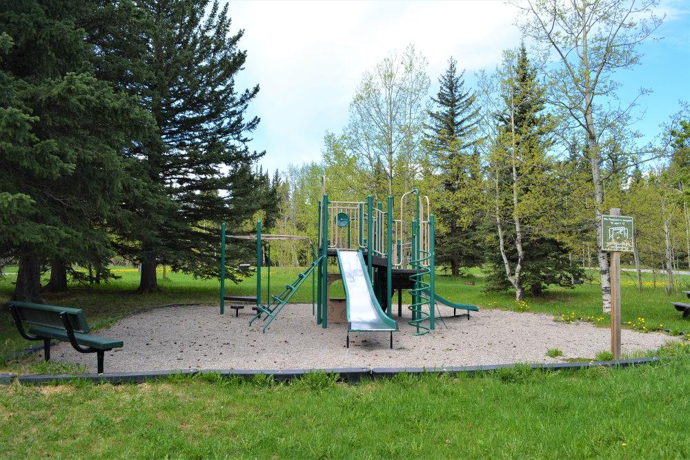 Green metal playground with slide and climbing aparatus