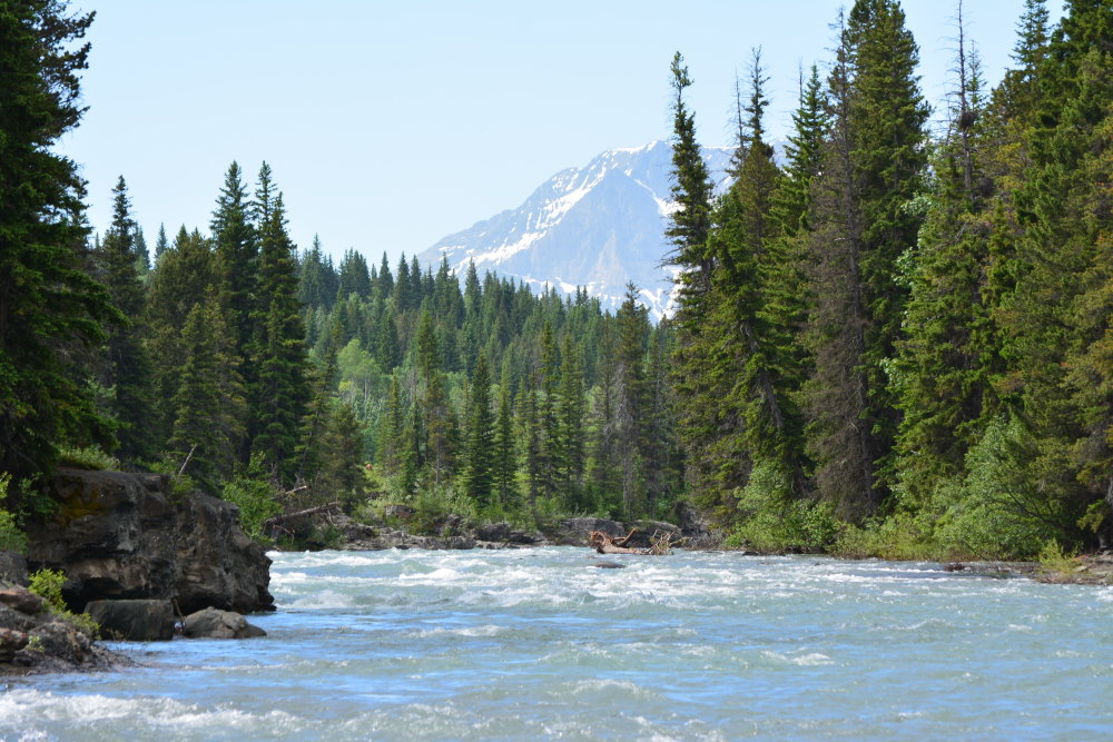 mountain behind rapid flowing river