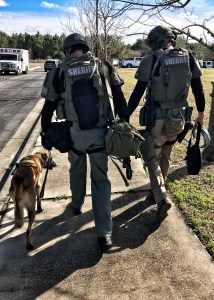 SWAT team members and a K-9 walking back after an incident