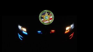 Alachua County Sheriff's Office Coin, with Patrol Car lights at night