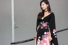 A katana-bearing geisha poses for photographers.