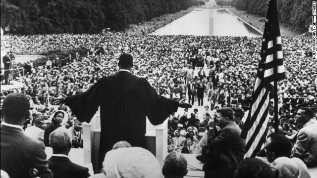March on Washington. Martin Luther King looking out onto thousands of faces, with his arms raised up.