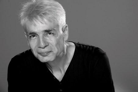 Un homme d'une cinquantaine d'année, Pierre-François Kettler, pose face public, le cou en avant, avec le sourire (grand format N&B)