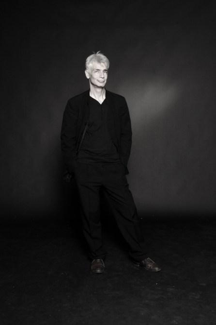 Un homme d'une cinquantaine d'année, Pierre-François Kettler, pose debout face public, décontracté, les mains dans les poches (grand format N&B)