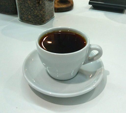 コーヒーカップに入ったコーヒーとその奥に写るコーヒー豆