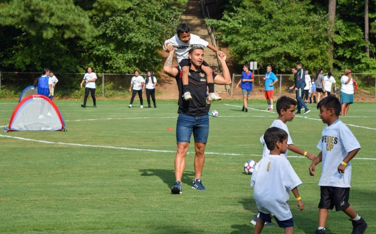 Atlanta United's Tito Villalba holds a child over his shoulder as he plays soccer with him during a soccer clinic after the unveiling of a new refurbished soccer field. #atlutd #titovillalba #soccer #mlssoccer #campeonescup