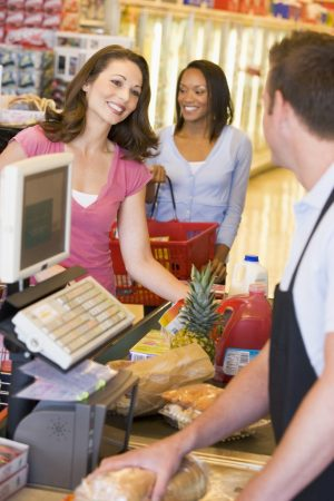 Woman paying for groceries at supermarket checkout
