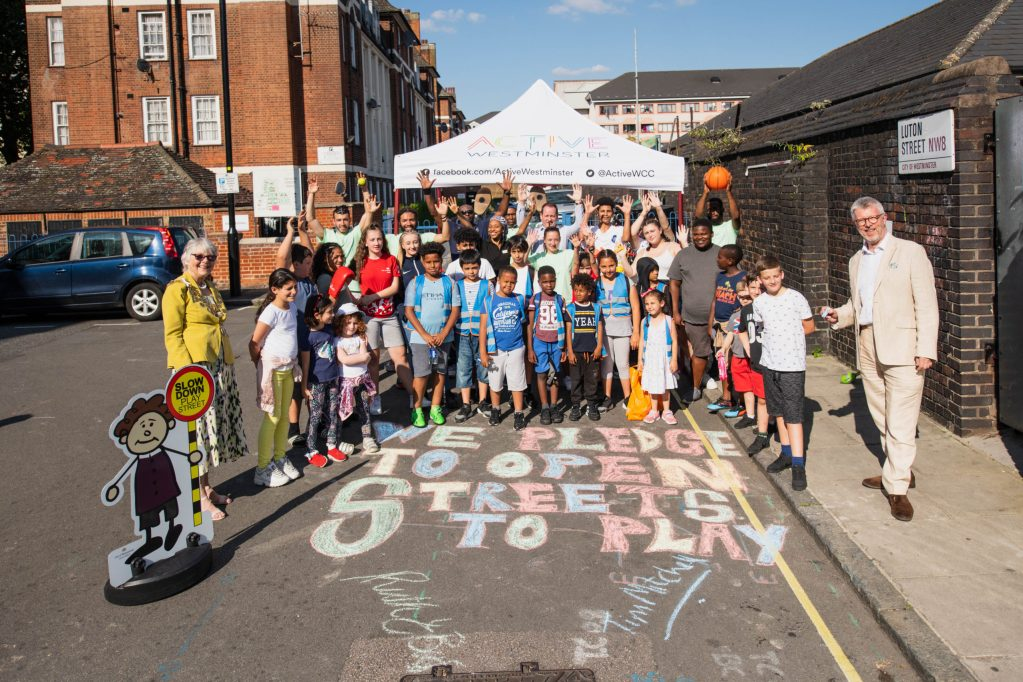 """Group of young children stood between two supervising adults, cheering in front of a colourful pledge written in chalk on the road. Pledge reads """"we pledge to open streets to play""""."""