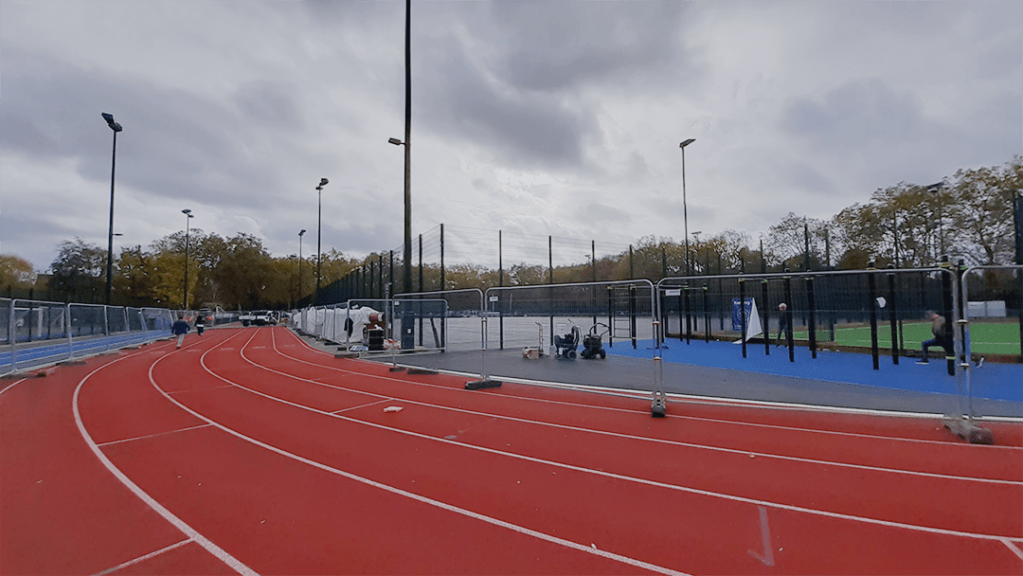 Metalic temporary construction fencing panelling along the inside of the athletics track at Paddington Recreation Ground