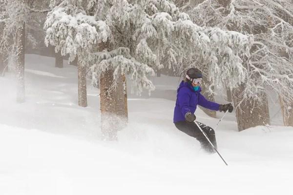 Mature woman (baby boomer generation) skiing through powder at Taos Ski Valley, New Mexico