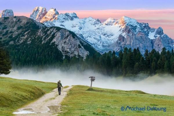 Hiker leaving Prato Piazza Rifugio along Alta Via 1 route at sunrise, Dolomites, Italy