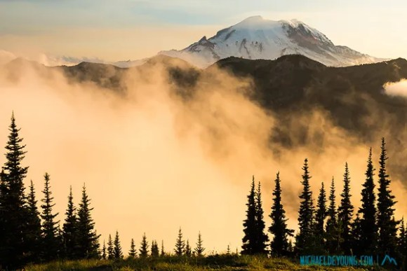 """Sunset and Mt. Rainier from Scout Pass on the PCT at 6500"""" with fog in valley below.  Forest fire smoke from fires in Washington and Oregon is seen over the summit."""