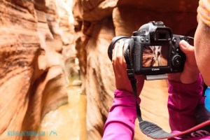 Photographer capturing image of swurvy canyon walls