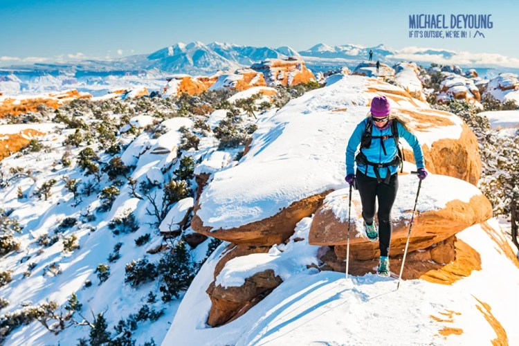 Hiker on snow covered trail to Double O Arch - Arches National Park, Utah.