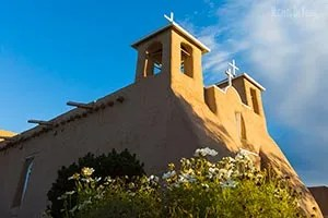 Flowers below the historic San Francisco de Asis Mission Church in Taos New Mexico