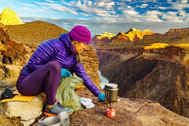 Woman cooking up backpacker breakfast with view of Hermit Rapids.  Grand Canyon National Park, AZ. Photo © Michael DeYoung