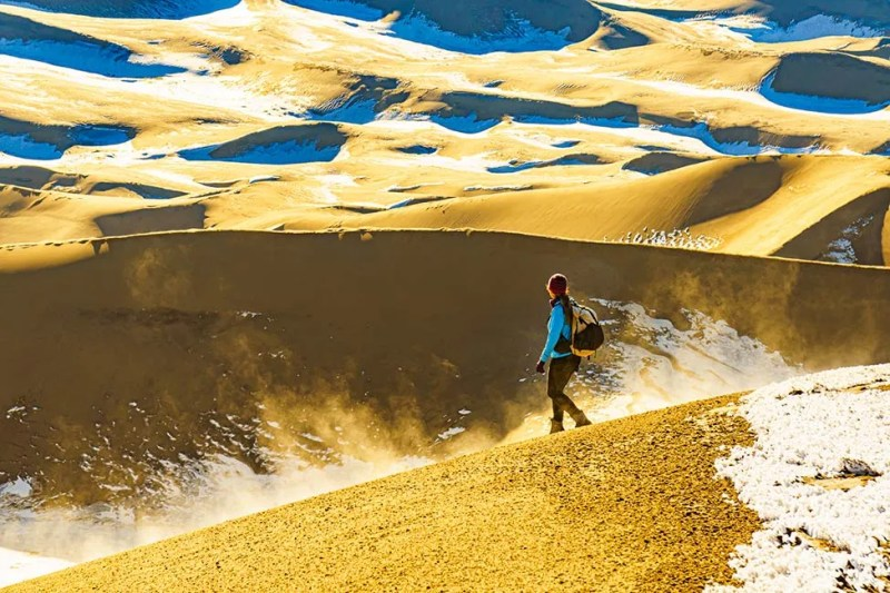 Hiker descending from High Dune in Great Sand Dunes National Park, Colorado. Photo © Michael DeYoung