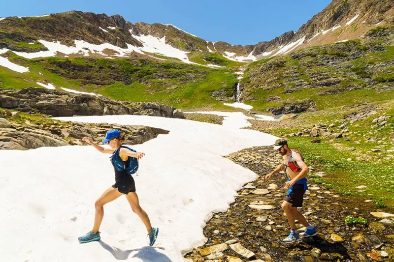 Couple hikers crossing snow field on mid summer hike near Crested Butte, Colorado. Photo © Michael DeYoung