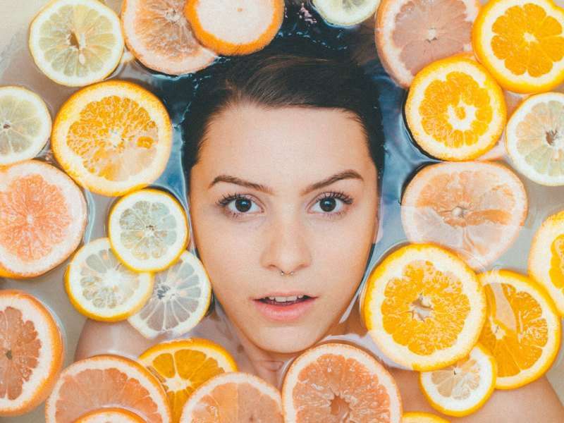 photo of a woman in a bath of lemons