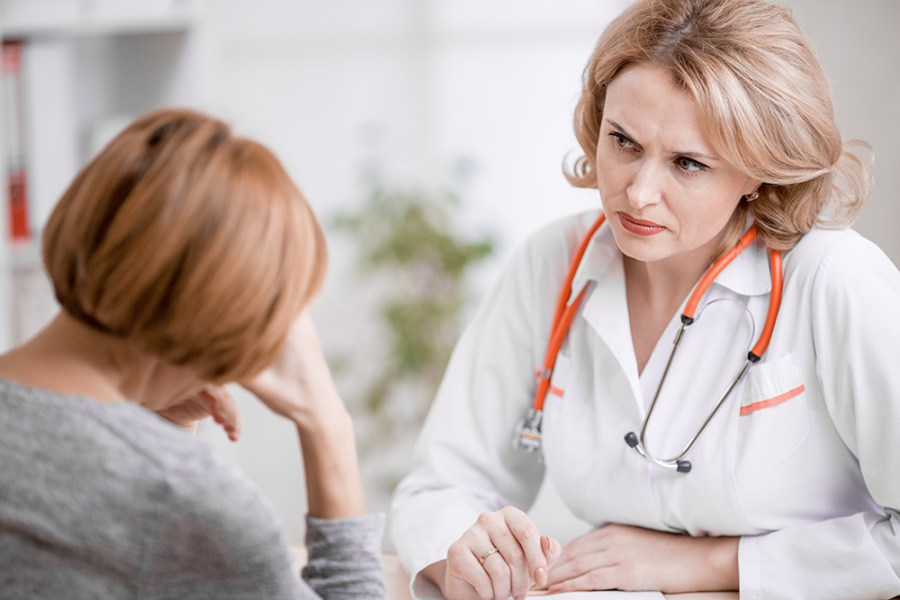 Serious doctor or physician looking at upset patient
