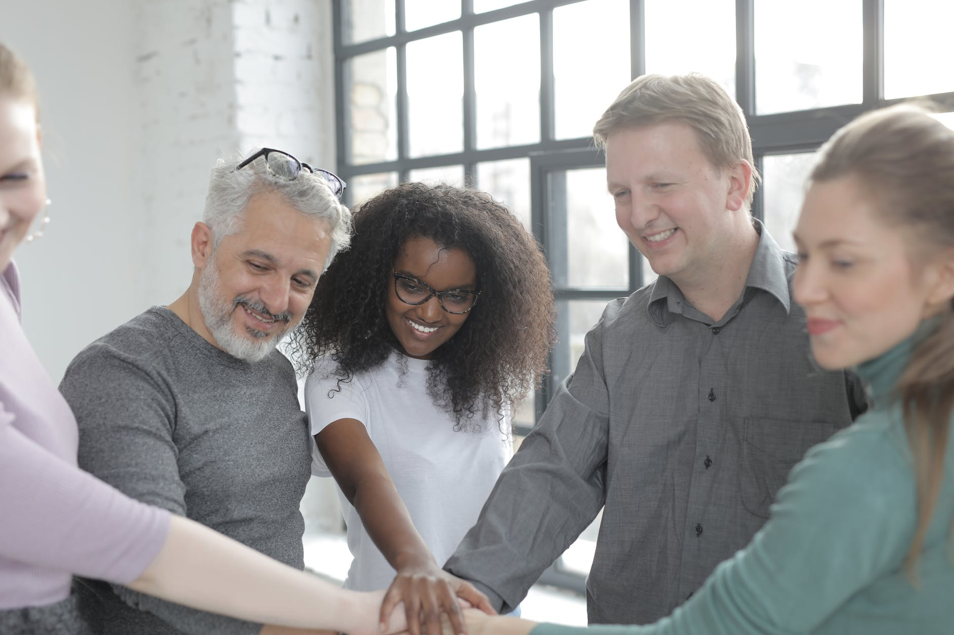 happy diverse colleagues joining hands at work in afternoon