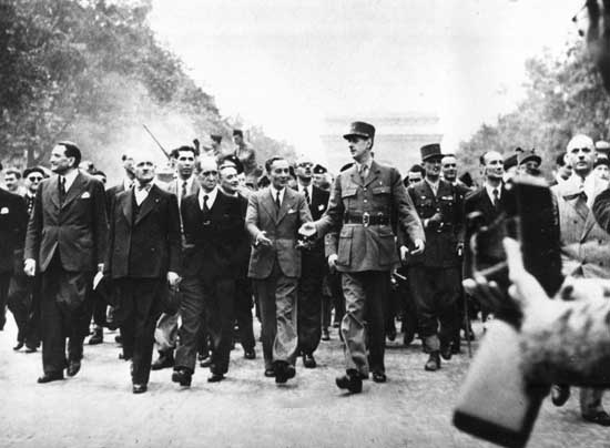 Gen. Charles de Gaulle, foreground wearing hat, leads a victory parade down the Champs Elysee in Paris, France, Aug. 31, 1944. De Gaulle talks with Gen. Jacques le Clerc, left, in the march to celebrate the Allied liberation of Paris from German forces in World War II. (AP Photo)