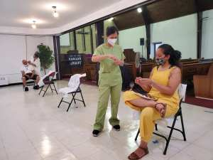 Picture of a NADA community clinic at Healing Space- Salud y Acupunctura Para el Pueblo (SAPP), FSUMC-People's Church featuring Karen in green scrubs and a few people who have received treatments.