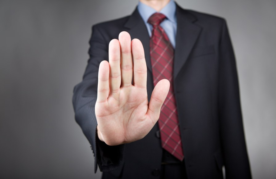 Man showing stop gesture. Neutral background