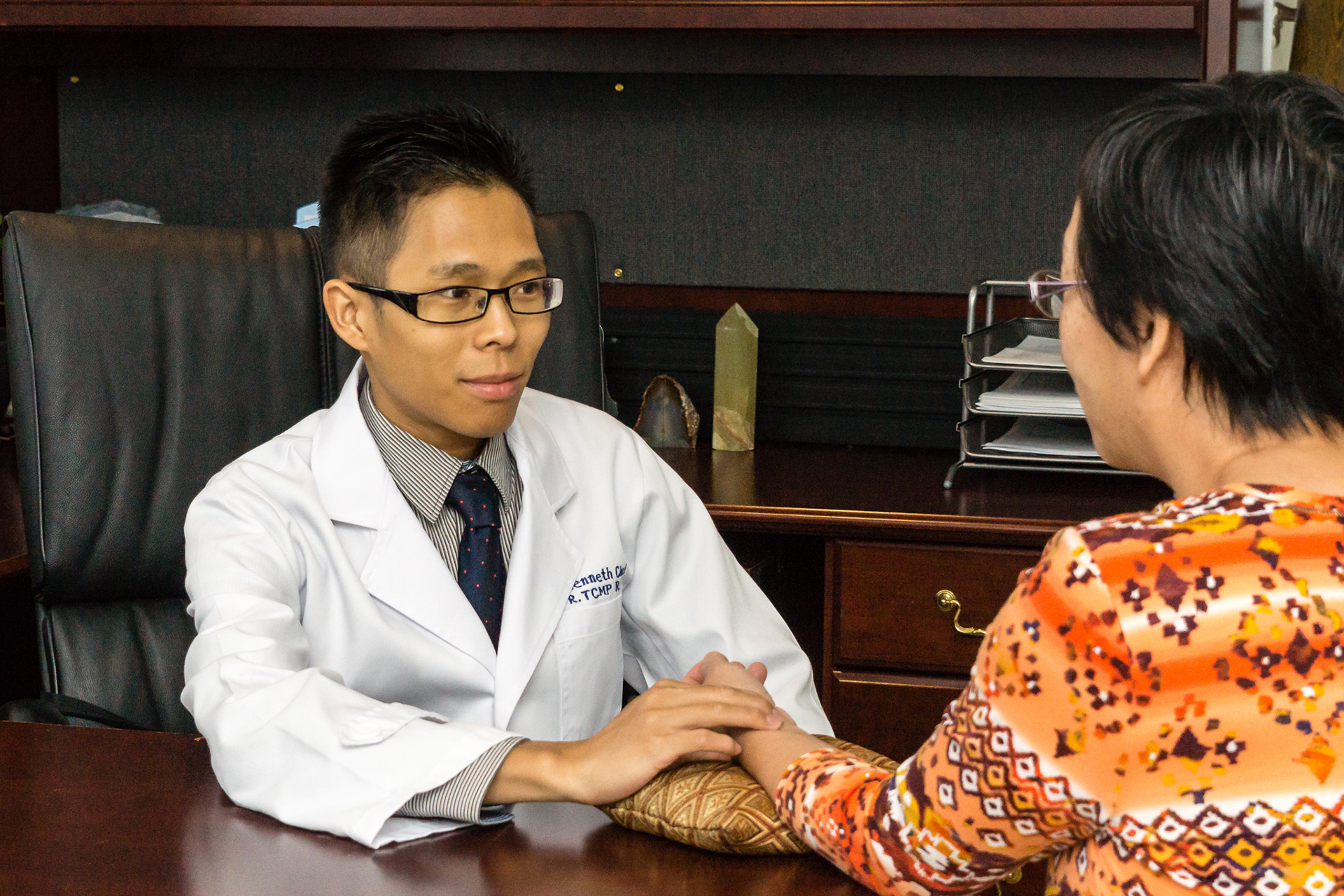 Acupuncturist Kenneth Choi examines a patient and provides advice