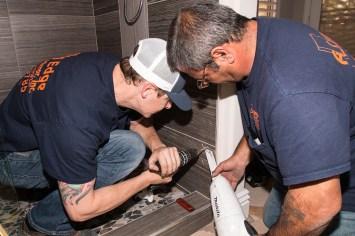 Close-up of Glaziers Installing Custom Shower Door