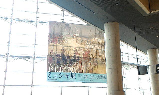 ガラスの壁に吊るされたミュシャ展の広告