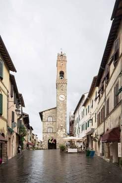 Platzverhältnisse: Der Turm des Palazzo dei Priori von Montalcino an einem regnerischen Tag im September. Die Pflastersteine der Piazza del Popolo sind dann sehr rutschig.