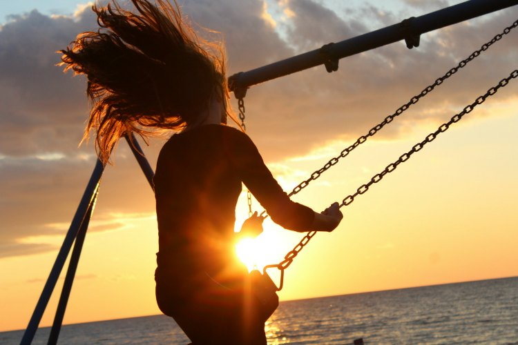 Girl swinging on swing set at sunset.
