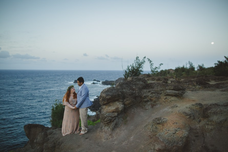 Interracial couple looking at each other lovingly on the cliffs in Kahakuloa Maui