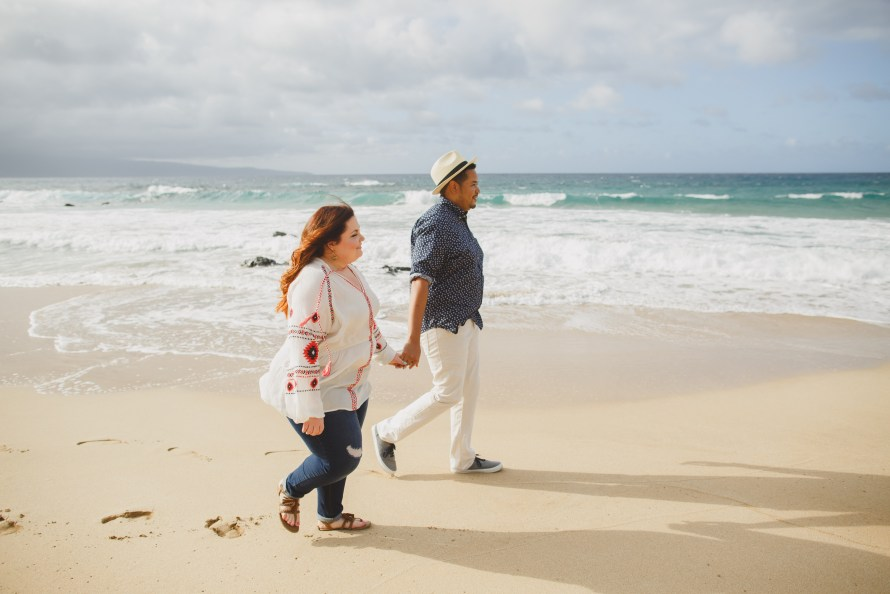 Interracial couple walking hand in hand on Oneloa beach, Maui