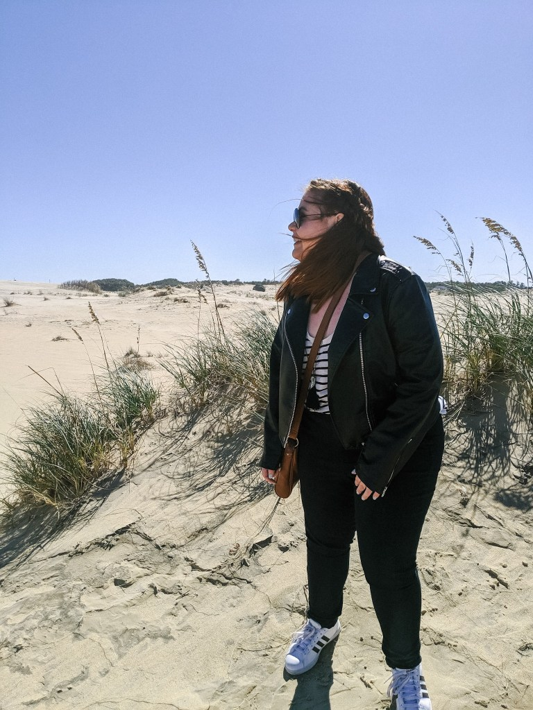 Girl standing on a sand dune with wind blowing in her face. She is smiling and happy.