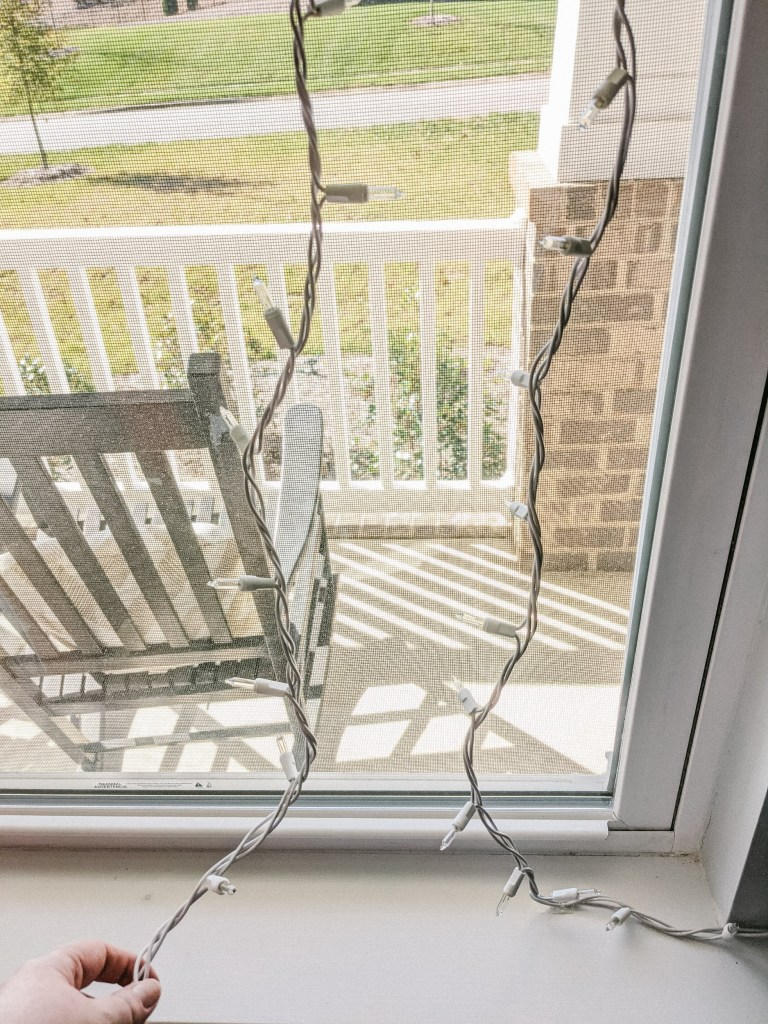 Window with two strings of Christmas lights attached and hanging down. A woman's hand holds the string to adjust the distance between them.
