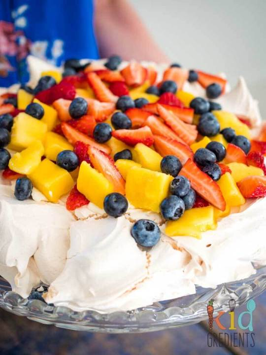 A traditional pavlova is pictured. Toasted meringue, mango, blueberries and strawberries are on top.